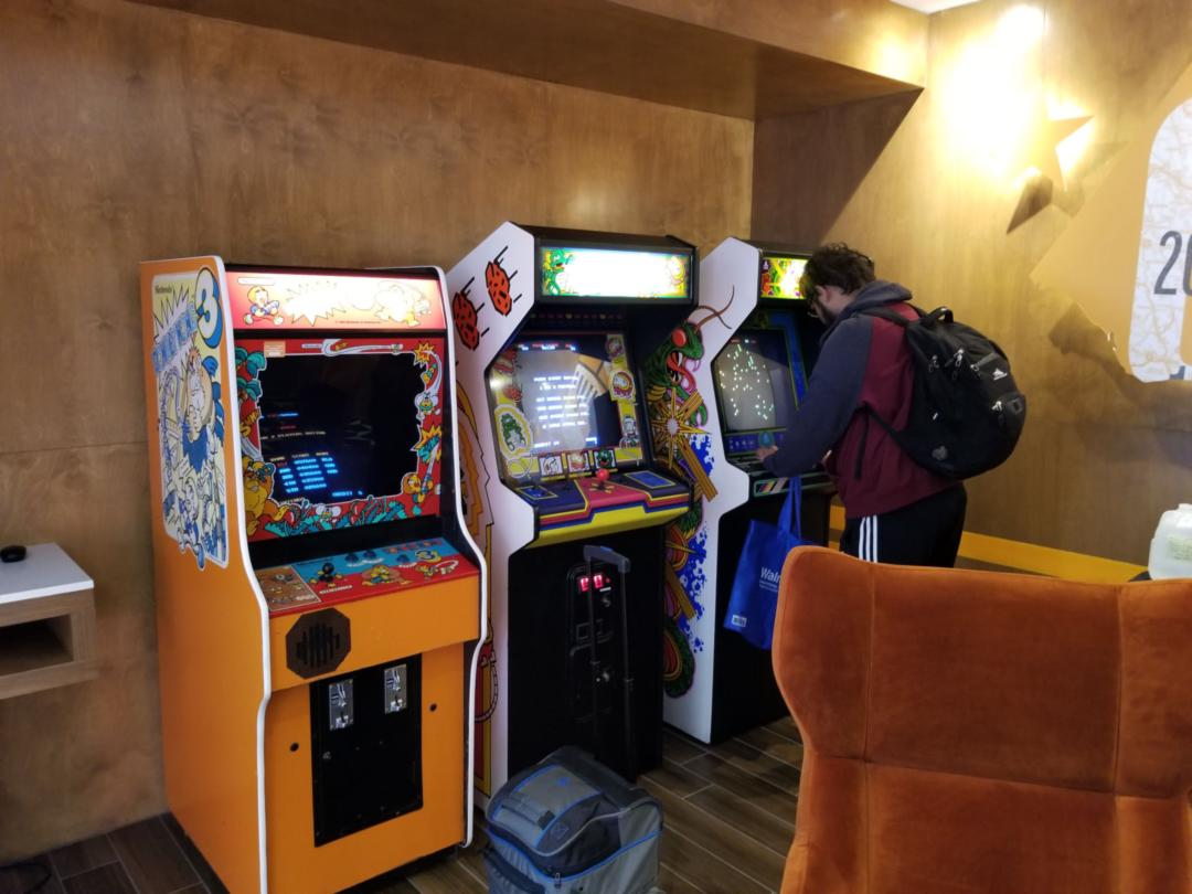 Three arcade cabinets with a token machine to their left