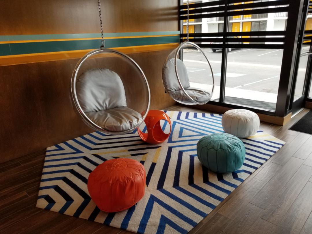 Modern-looking circle chairs surrounded by cloth stools in a hotel lobby