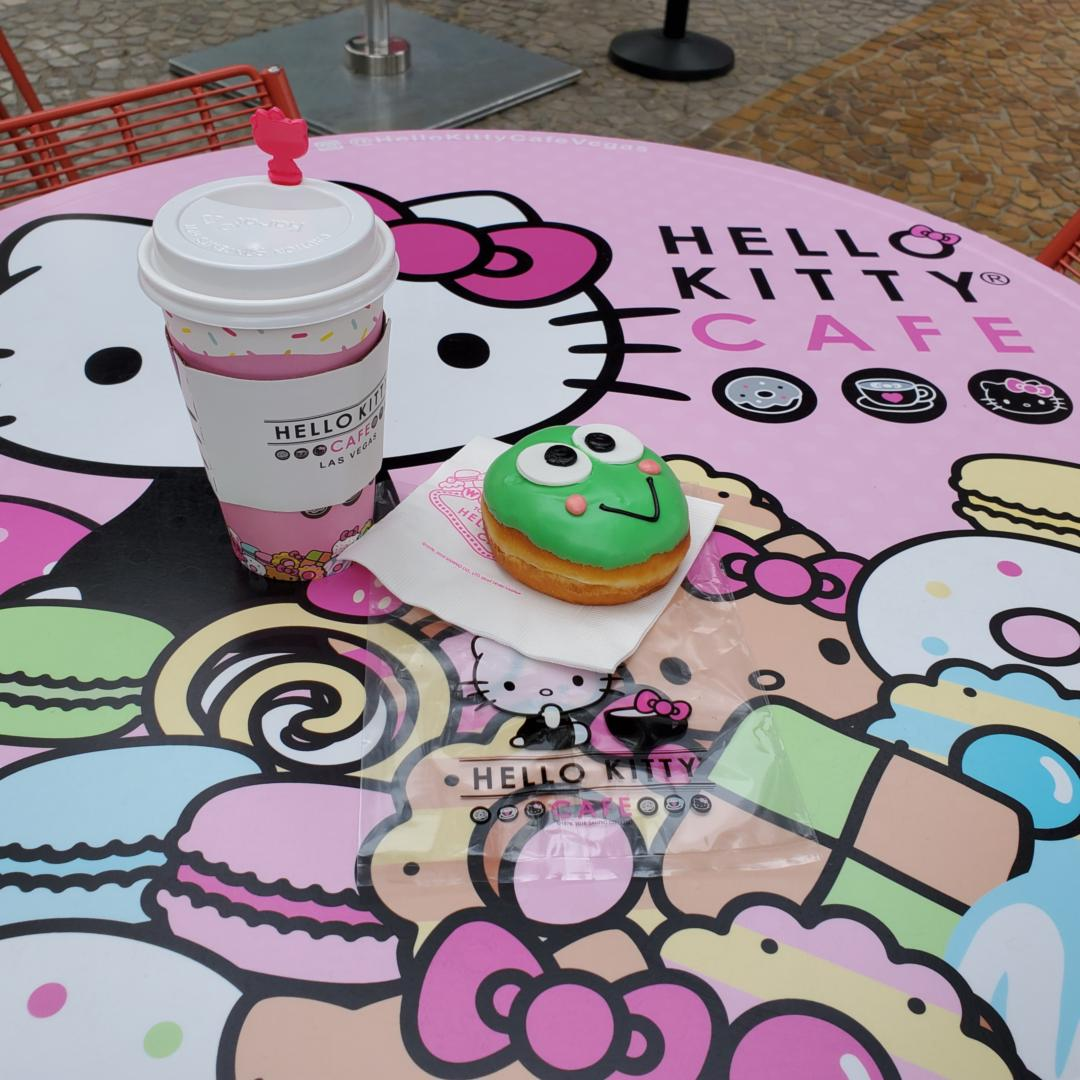 Atop a Hello Kitty Cafe table is a pistachio donut shaped like Keroppi Frog and a paper take-away cup that has a white mocha inside.